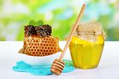 Sweet honeycombs in bowl and bank with honey on wooden table on natural background