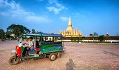 VIENTIANE, LAOS - 11 DEC,2013: Unidentified tuk tuk taxi driver near golden pagoda wat Phra That Lua