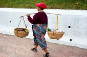 LUANG PRABANG, LAOS - 8 DEC, 2013: Unidentified woman sells goods by using traditional baskets on th