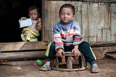LUANG PRABANG, LAOS - 9 DEC, 2014: Unidentified two kids in traditional village of Laos. Eco tourism