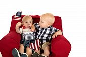 Toddler Boys Sitting In A Red Chair Holding American Flags