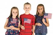 Portrait Of Cute Caucasian Children Holding American Flags Smiling