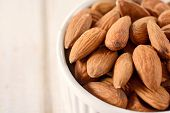 picture of vegan  - Heap of almonds in the bowl and blank space on the left side - JPG