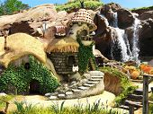 Hobbit or fairy town by a majestic waterfall.