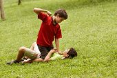 Violent Kid Fighting And Hitting Scared Boy In Park
