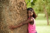 Portrait Of Black Ecologist Girl Hugging Tree And Smiling