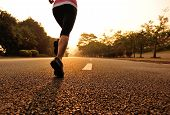 runner athlete legs running on sunrise road