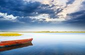 image of boggy  - boat on the bank of lake on sunset - JPG