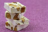 Almond nougat on pink background with copy space