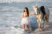 smiling young woman walking with a white horse on beach