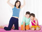 stock photo of pillow-fight  - mother and her two sons having a pillow fight in bedroom - JPG