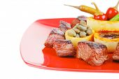 european food: roast beef meat over red plate isolated on white background with hot peppers, capers