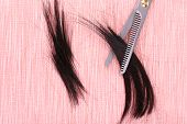 Cut hair and scissors on tile background