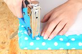 Fastening fabric and board using construction stapler