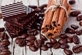 chocolate sweets, cinnamon and coffee beans on rustic wooden background