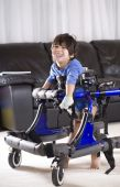 image of physically handicapped  - Disabled child in walker standing up in his walker - JPG