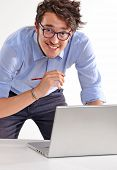 Successful young businessman wearing eyeglasses working on computer laptop on white background.