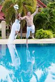 Newlyweds Jumping In Swimming Pool