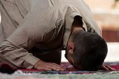 picture of muslim  - Young Muslim Man Making Traditional Prayer To God While Wearing A Traditional Cap Dishdasha - JPG