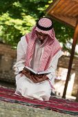 Muslim Man In Dishdasha Is Reading The Quran