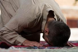 foto of muslim man  - Young Muslim Man Making Traditional Prayer To God While Wearing A Traditional Cap Dishdasha - JPG