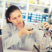 image of robot  - schoolgirl adjusts the robot arm model - JPG