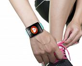 Woman Hand Tying Shoelaces Wearing Bright Blue Watchband Touchscreen Smartwatch