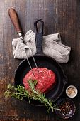 Raw Meat Ribeye Steak, Seasonings And Meat Fork On Cast Iron Frying Pan On Wooden Background