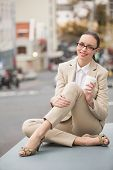 Young businesswoman holding take away coffee outside in the city
