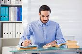 Businessman reading book while writing at his desk in the office