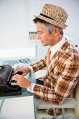 Vintage man in straw hat typing on typewriter in his office