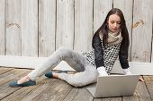 Pretty hipster using her laptop against bleached wooden planks