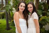 Pretty friends smiling at camera in white dresses outside in the garden
