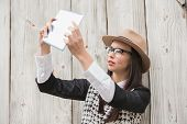 Pretty hipster using tablet pc against bleached wooden planks