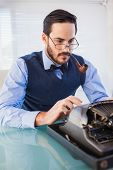 Businessman with pipe in his mouth working on typewriter in the office