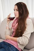 Pretty brunette drinking wine on couch at home in the living room