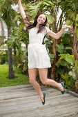 Pretty brunette jumping up and smiling outside in the garden