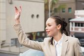 Young businesswoman hailing a cab outside in the city