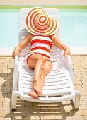 Young Woman Laying On Sunbed With Hat On Head