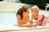 Portrait Of Happy Mother And Baby Girl At Poolside