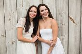 Pretty friends smiling in white dresses against bleached wooden planks