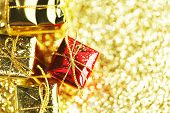 Decorative boxes with holiday gifts on abstract gold background