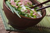 Pho Bo Soup With Beef Rare, Rice Noodles And Fresh Herbs Closeup