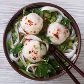 Traditional Soup With Fish Balls And Rice Noodles Closeup. Top View