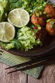Fish Balls With Lime And Salad And Chopsticks Close-up. Vertical