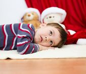 Cute Boy Daydreaming Lying On The Floor. New Year