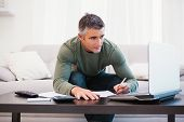 Concentrated man using laptop and taking notes at home in the living room