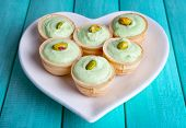 Tartlets with greens and sauce on plate on table