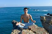asian man acts yoga sitting on the beach in the morning
