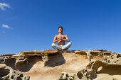 Portrait of handsome man doing yoga exercise in outdoors